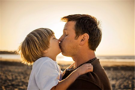Father kissing son at the beach Stock Photo - Premium Royalty-Free, Code: 6128-08747880