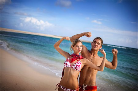 Happy young couple flexing their muscles on a beach. Stock Photo - Premium Royalty-Free, Code: 6128-08747951
