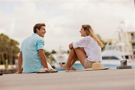 Smiling young couple sitting together on a jetty. Stock Photo - Premium Royalty-Free, Code: 6128-08747901