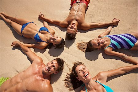 Five laughing people holding hands while lying in the shape of a star on a sandy beach. Stock Photo - Premium Royalty-Free, Code: 6128-08747915
