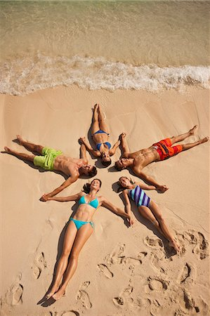 Five laughing people holding hands while lying in the shape of a star on a sandy beach. Stock Photo - Premium Royalty-Free, Code: 6128-08747916