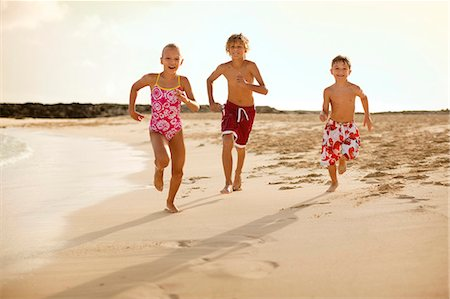 preteen boy shirtless - Portrait of three smiling children running together along a sandy beach wearing bathing suits. Stock Photo - Premium Royalty-Free, Code: 6128-08747939