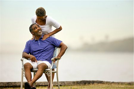 Mature man receiving shoulder massage from his wife by the beach. Stock Photo - Premium Royalty-Free, Code: 6128-08748097