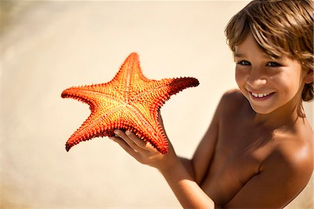 Portrait of a smiling young boy showing off a starfish that he has found. Stock Photo - Premium Royalty-Free, Code: 6128-08748002