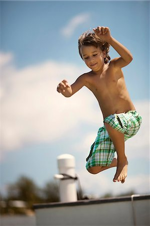 Smiling young boy leaping from a pier into the water. Stock Photo - Premium Royalty-Free, Code: 6128-08748006