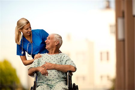 Young doctor and her elderly patient laughing together as she pushes him in a wheelchair. Stock Photo - Premium Royalty-Free, Code: 6128-08748167