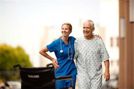 Young doctor and her elderly patient laugh together as she assists him with walking outside. Stock Photo - Premium Royalty-Free, Code: 6128-08748168