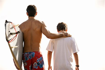 preteen boy shirtless - Mid adult man walking with his arm around his teenage son while carrying a surfboard along a beach. Stock Photo - Premium Royalty-Free, Code: 6128-08748127