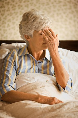 Senior woman sitting in bed presses her forehead with her hand as if to release the pressure of a headache. Stock Photo - Premium Royalty-Free, Code: 6128-08766986