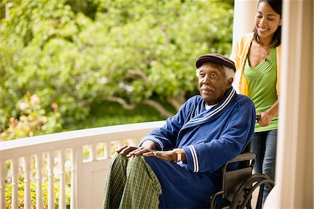 Smiling woman pushes a senior man in a wheelchair along a porch. Stock Photo - Premium Royalty-Free, Code: 6128-08766924
