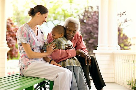 Nurse looks on happily as a senior man hugs a boy and she puts a supportive hand on the boy's arm. Stock Photo - Premium Royalty-Free, Code: 6128-08766937