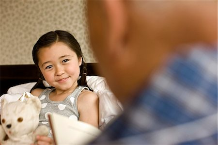 Grandfather reads to his granddaughter while she is ill in bed. Stock Photo - Premium Royalty-Free, Code: 6128-08766939