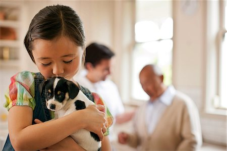 dog kissing girl - Young girl holding a puppy. Stock Photo - Premium Royalty-Free, Code: 6128-08767041
