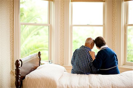 Senior couple sitting on bed both in dressing gowns. Stock Photo - Premium Royalty-Free, Code: 6128-08767031