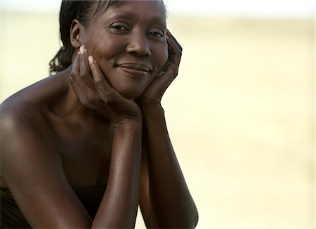 An African woman cupping her face. Stock Photo - Premium Royalty-Free, Code: 6128-08780348