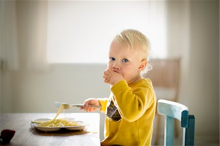 Portrait of a young toddler sitting at a dining table eating a plate of plain spaghetti. Stock Photo - Premium Royalty-Free, Code: 6128-08780456