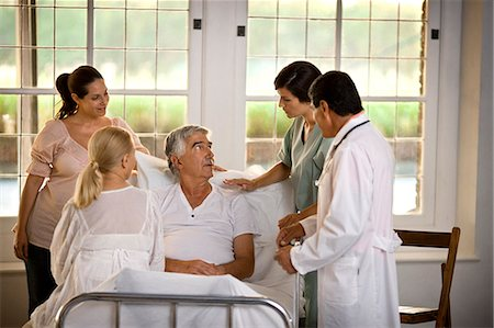 Elderly man receiving a hospital visit from his family. Stock Photo - Premium Royalty-Free, Code: 6128-08780750