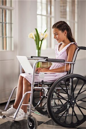 Young girl sitting in wheelchair typing on laptop. Stock Photo - Premium Royalty-Free, Code: 6128-08780784