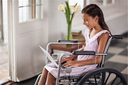 Young girl sitting in wheelchair typing on laptop. Stock Photo - Premium Royalty-Free, Code: 6128-08780785