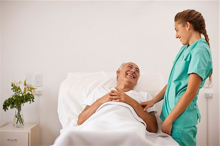Female nurse laughing with senior male patient lying in hospital bed. Stock Photo - Premium Royalty-Free, Code: 6128-08780793