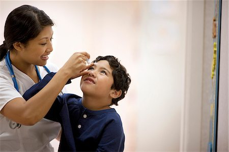 Nurse administering eye drops to a young boy. Stock Photo - Premium Royalty-Free, Code: 6128-08780986