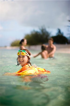 preteen boy shirtless - Portrait of a smiling young girl swimming with her family at a tropical beach. Stock Photo - Premium Royalty-Free, Code: 6128-08798798