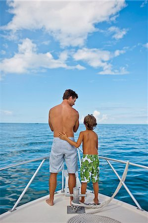 father son shirtless - Father and young son looking out to sea while on a boat. Stock Photo - Premium Royalty-Free, Code: 6128-08798872