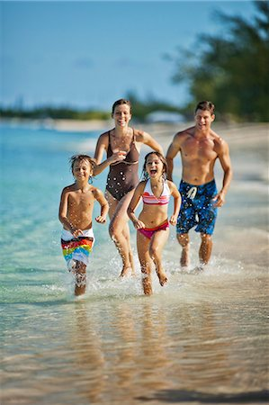 preteen boy shirtless - Happy family splashing in shallow water at a tropical beach. Stock Photo - Premium Royalty-Free, Code: 6128-08798812
