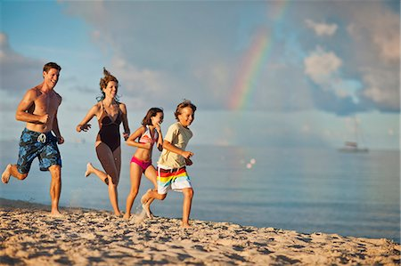 preteen boy shirtless - Happy family running on the sand at a tropical beach. Stock Photo - Premium Royalty-Free, Code: 6128-08798814