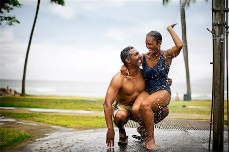 Couple showering under beach shower Stock Photo - Premium Royalty-Free, Code: 6128-08798963