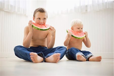 preteen boy shirtless - Two brothers dressed identically and eating watermelon Stock Photo - Premium Royalty-Free, Code: 6128-08727435