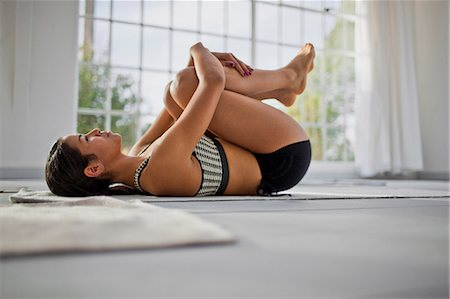 Young woman hugging her knees to her chest after a yoga session. Stock Photo - Premium Royalty-Free, Code: 6128-08727623