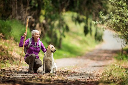 senior lady walking - Portrait of a cheerful mature woman taking a break from hiking in the forest to pet her dog. Stock Photo - Premium Royalty-Free, Code: 6128-08728017
