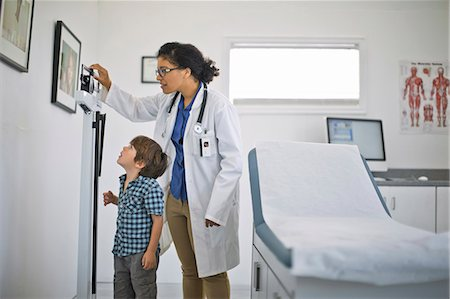 Doctor showing a little boy his height on a ruler. Stock Photo - Premium Royalty-Free, Code: 6128-08728038