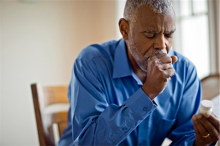 people coughing or sneezing - Sick man looks at pill bottle whilst coughing Stock Photo - Premium Royalty-Free, Code: 6128-08728248