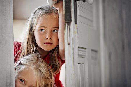 Two young girls peering around a doorframe. Stock Photo - Premium Royalty-Free, Code: 6128-08728298