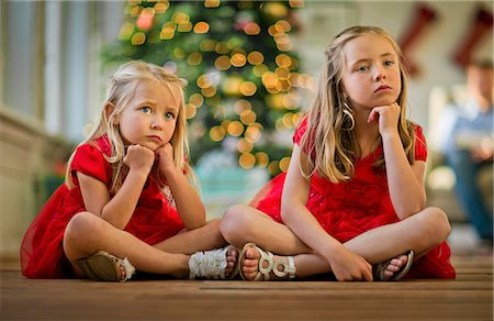 sad girls - Two bored young girls waiting to open their Christmas presents. Stock Photo - Premium Royalty-Free, Code: 6128-08728312