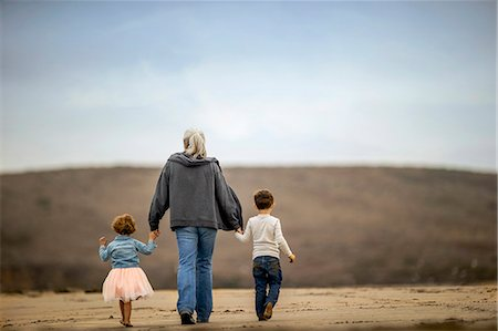 rear - Mature woman walking on the beach with her grandchildren. Stock Photo - Premium Royalty-Free, Code: 6128-08728408