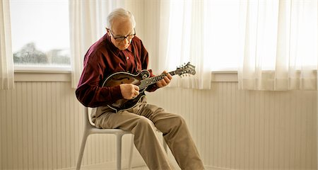 Senior man playing a guitar inside a room. Stock Photo - Premium Royalty-Free, Code: 6128-08737639