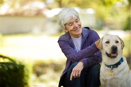 dog and woman and love - Smiling senior woman petting her dog in her garden. Stock Photo - Premium Royalty-Free, Code: 6128-08737813