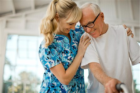 Happy young nurse comforting a senior man. Stock Photo - Premium Royalty-Free, Code: 6128-08738064