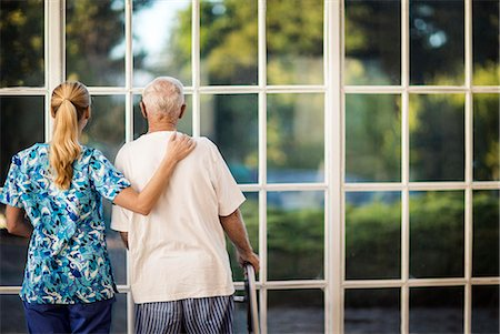 Nurse and her patient looking out of a window. Stock Photo - Premium Royalty-Free, Code: 6128-08738072