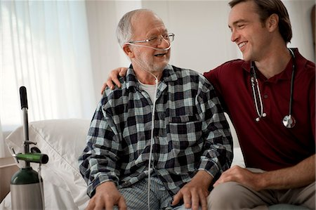 Cheerful elderly man with a nasal tube speaking with a male nurse at his hospital bed. Stock Photo - Premium Royalty-Free, Code: 6128-08738172