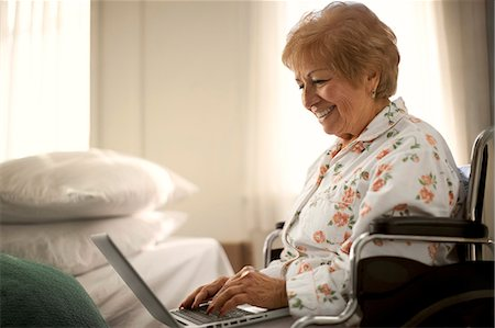 Smiling senior woman having fun using a laptop while sitting in a wheelchair. Stock Photo - Premium Royalty-Free, Code: 6128-08738187