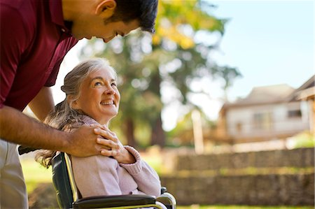 Smiling senior woman being comforted by a male nurse while sitting in a wheelchair inside a park. Stock Photo - Premium Royalty-Free, Code: 6128-08738197