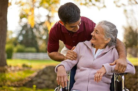 Smiling senior woman being comforted by a male nurse while sitting in a wheelchair inside a park. Stock Photo - Premium Royalty-Free, Code: 6128-08738196