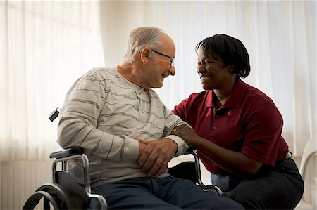 Smiling female nurse comforting an elderly male patient in a wheelchair. Stock Photo - Premium Royalty-Free, Code: 6128-08738198