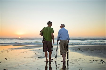 Senior man with a walking aid on the beach with his son and grandchild. Stock Photo - Premium Royalty-Free, Code: 6128-08738132