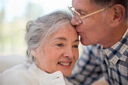 Smiling senior woman being kissed on the forehead by her husband. Stock Photo - Premium Royalty-Free, Code: 6128-08738201