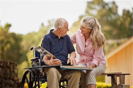 Smiling mature woman looking through a photo album with her senior husband. Stock Photo - Premium Royalty-Free, Code: 6128-08738391